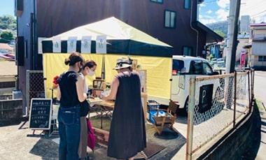 青空の下で新刊書を販売する「道草書店」の写真