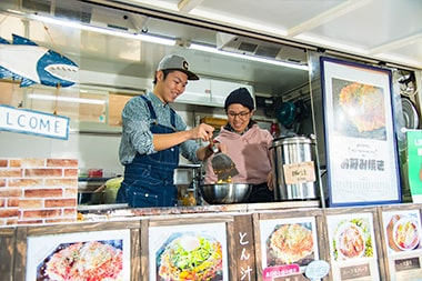 キッチンカーでお好み焼きを焼く「Sunny Side Kitchen」安藤亮太さん夫婦の写真