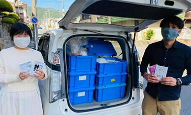 「道草書店」の準備のため車に本を積む中村竹夫さん、道子さん夫妻の写真