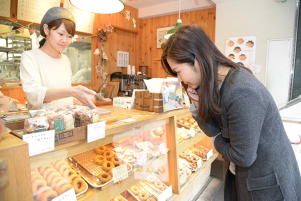 店頭に並ぶドーナツを見ているレポーター