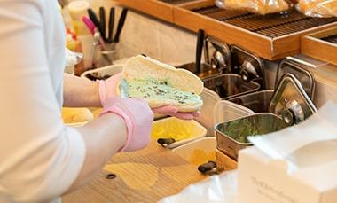 コッペパン専門店「月刊アベチアキ」の阿部千秋さんがオススメメニューの1つチョコミントを作っている写真